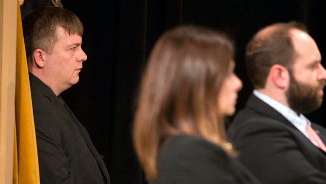 Fired police officer Christopher Manney, left, listens as a panel of three Fire and Police Commission members uphold his dismissal at Centennial Hall in Milwaukee on Monday.