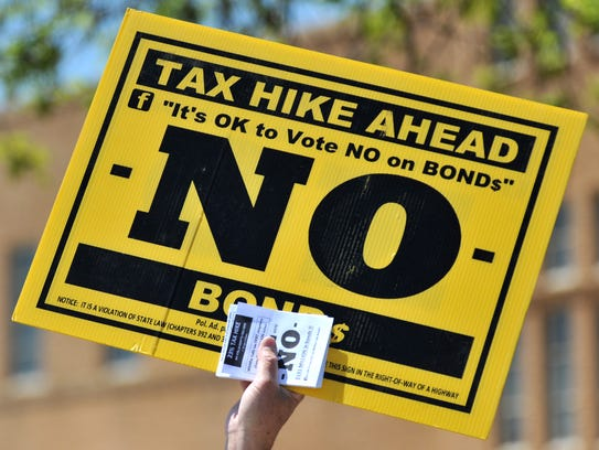 Signs are held in protest of a possible tax increase