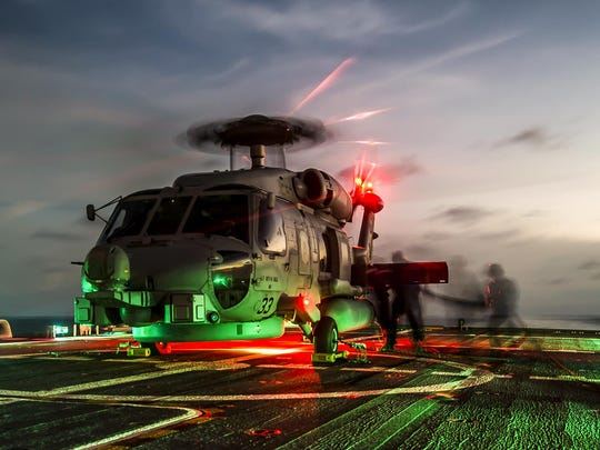 Sailors refuel an MH-60R Seahawk helicopter on the flight deck of the USS Fort Worth in April. Fort Worth is on a 16-month rotational deployment in the Far East.