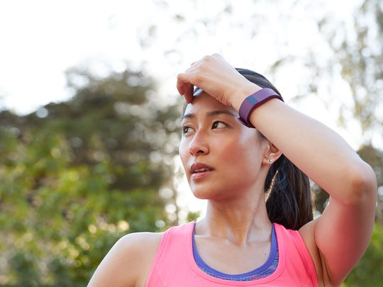 A runner pauses for a break while wearing a Fitbit wearable technology device in this image provided by Fitbit.