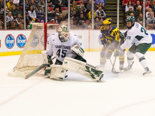 Michigan's Sam Piazza looks on as Michigan State goalie Ed Minney tries to stop the puck from squeaking through his legs Friday, Feb. 10, 2017 at Joe Louis Arena. U-M won 5-4 in a shoot-out.