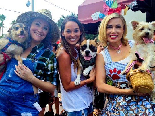 The Humane Society of the Treasure Coast's Pup Crawl is this weekend in downtown Stuart. From left, Kellie Berthiaume with Pizza Beans, Katie Brezinski with Max and Taylor Emerick with Max are pictured at last year's pup crawl.