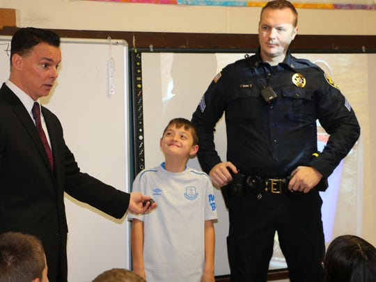 In this file photo, Highland Elementary School fifth-grader Hunter Baran helps Town of Lloyd Police Chief Daniel Waage, left, and Police Sgt. Philip Roloson make a point about the dangers of narcotics during a December 2017 presentation at the school.