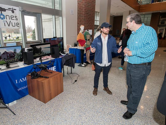 MTSU junior Gerardo Salinas, wearing cap, talks with management professor Cliff Welborn about Salinas' business plan during the March 28 Business Plan Trade Show preliminary competition held in the Student Union Atrium.