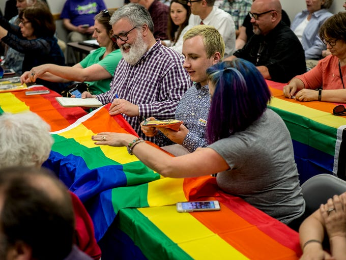 People layout pride flags on tables before the start