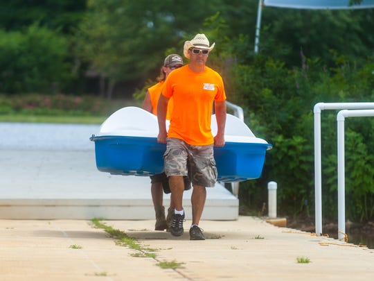 Mike Martin and son Michael Martin take out a paddle boat for Cowboy Mike's Canoe Rental at Cooper River Park on Saturday, July 15.