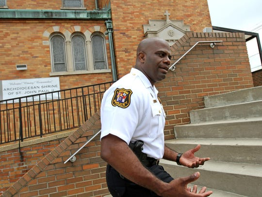 Linden Police Captain Jonathan Parham talks about his upcoming security awareness seminar on August 19, for houses of worship, as he takes a walk around the grounds of St Theresa's Church in Linden.
