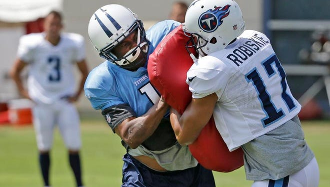 Titans receivers coach Shawn Jefferson, left, wears a helmet, pads and a jersey as he serves as a blocker against wide receiver Brian Robiskie during a drill on Tuesday at Saint Thomas Sports Park.