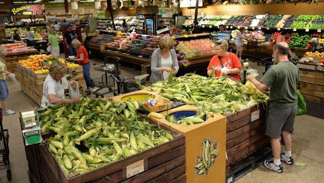 Customers shop for corn at the Wegmans in Fairfax, Va.