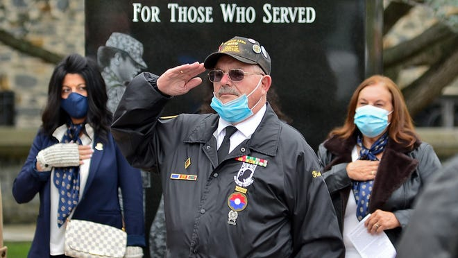 """Henry """"Hank"""" Mello salutes during the singing of the National Anthem at the rededication ceremony of the Taunton Desert Shield/Desert Storm monument held Sunday Nov. 1, 2020.  Taunton Gazette   Mike Borden"""