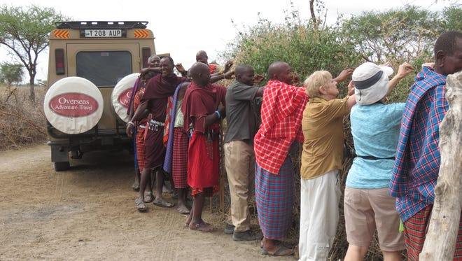 Travelers with the Overseas Adventure Travel tour in Tanzania help Massai tribespeople string lights around their cattle barriers. The lights keep predators away.