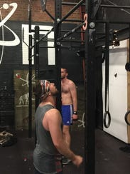 """Jimmy Dotson eyes the bar before jumping up for his next set of pull-ups while completing the Memorial Day """"Murph"""" workout at Crossfit Reaction in Greenville on Monday."""