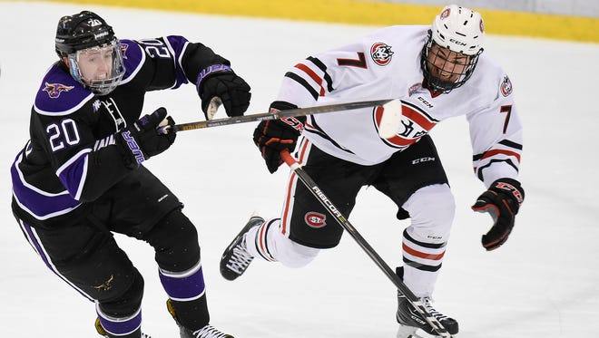 Minnesota State Mankato's Marc Michaelis and St. Cloud State's Mick Poehling chase a loose puck during the first period Saturday, Jan. 20, at the Herb Brooks National Hockey Center.