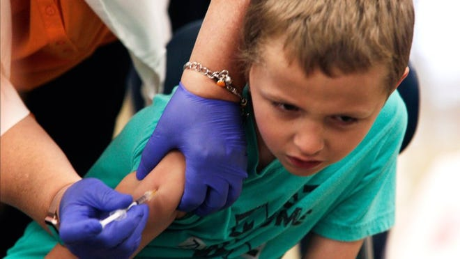 Devon Paige, 6, turns away as he gets immunized during Free Flu Shot Saturday at Farragut High School.