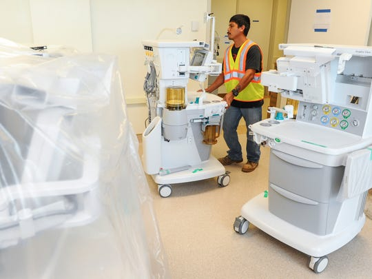In this file photo, a Guam Regional Medical City bio-medical apprentice wheels a medical device in a room for temporary storage.