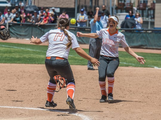 Aztec's Sarrah Jones. right, and Paige Adair celebrate after recording the final out of the 5A state softball championship against Artesia on Saturday in Albuquerque.