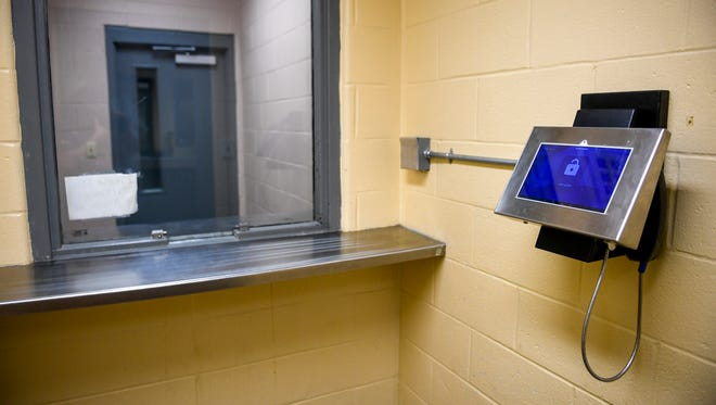 """A tablet installed to submit requests to speak over the phone is in the room dividing visitors, including bail bondsmen, from inmates at Madison County Jail in Jackson, Tenn., on Wednesday, Aug. 29, 2018. """"On the other side of that glass is the free world"""" Capt. Rudder said."""