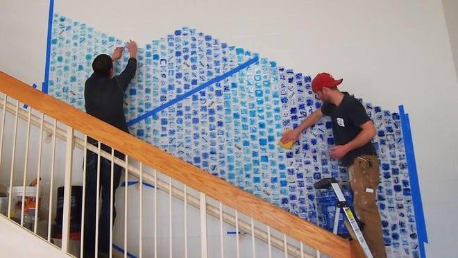 Workers from Brazee Street Studios in Cincinnati install the 88-tile mural at Burlington Elementary.
