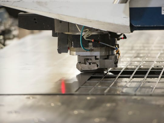 A computerized puncher stamps pieces out of sheet metal at Marlin Steel in Baltimore, which has embraced automation to remain competitive against foreign manufacturers.