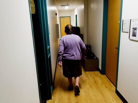 Blanca Simonian walks down a hallway to see a patient