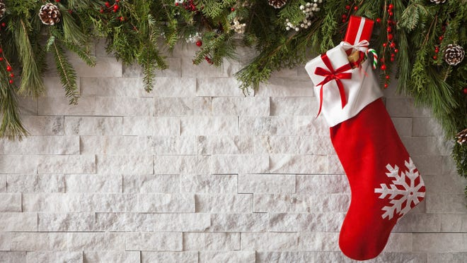 Christmas Stocking with gifts and bow hung on a fireplace with evergreen garland.