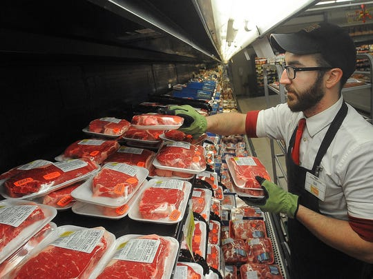 Bill Squwer an employee at Sunshine Foods stocks the