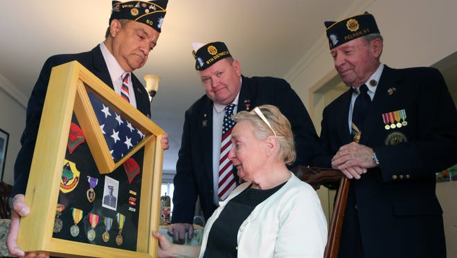 Margie DiSapio of Pelham reacts to the presentation case containing medals and ribbons that were earned by her brother-in-law, Marine Lance Corporal Donald A. DiSapio, who was killed in action in Vietnam in 1966. The medals were stolen a decade ago, but restored through the efforts of members of the American Legion Post 50. Presenting the case were Post members Bill Aguilar, Bob McGuirl and Joe Hall.
