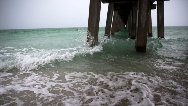 Waves crash against the Naples Pier as rain rolls in Monday, June 5, 2017, in downtown Naples.
