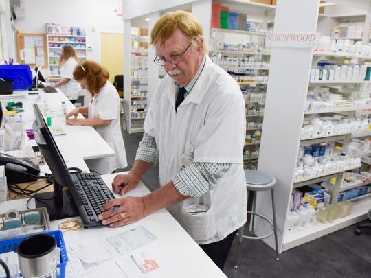 Pharmacist Russell Johnson checks out a prescription