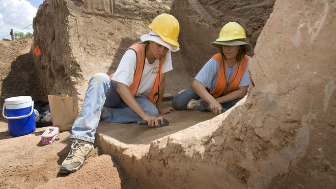 145992 -- asudig07 -- 7/27/07 -- Physical anthropologist  (left) Shayna Coe and Erica O'Neil dig on the northwest corner of Rural and Apache in Tempe, removing broken pottery.  Photo by Cheryl Evans / THE ARIZONA REPUBLIC  (8/2/07 Anthropologists Shayna Coe and Erica O'Neil dig through soil and collect pottery to be handed over to ASU's Archaeological Research Institute)