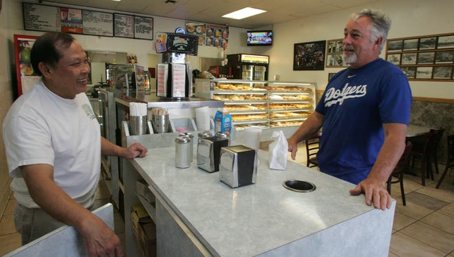 Heng Chauv, the owner of Donuts Plus, talks with longtime customer Kevin Lampson on Friday in Simi Valley. Chauv was initially concerned when rumors of a Dunkin' Donuts started to circulate, but he's received reassurance from loyal customers.