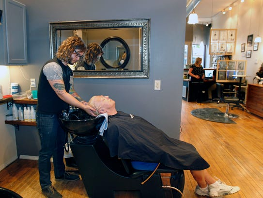 Joe Szozda, a stylist at Tease Salon in Bay View, washes