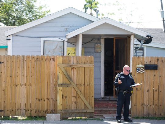 An officer stands outside a home as Corpus Christi