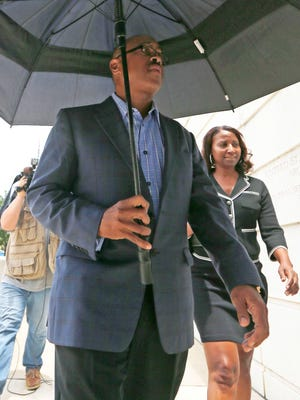 Dr. Carl Reddix, 57, left, and his attorney Lisa Ross use an umbrella to hide under as he attempts to avoid reporters while entering the federal courthouse in Jackson, Miss., Wednesday, July 20, 2016 where federal prosecutors indicted him on charges of bribing former Mississippi Corrections Commissioner Christopher Epps. Reddit is charged with six counts of bribery and one count of conspiracy to commit honest services wire fraud.
