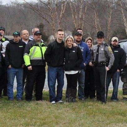 Deputy Scott Hogan (center, with a black jacket and
