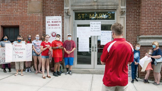 Bob Prytko, center, leads a prayer outside the St. Mary's School in Worcester. Prytko is a parent of current and past students at the Catholic school.
