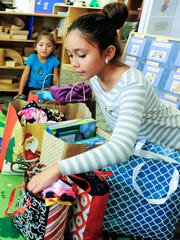 Lillyanna Martinez, 10, picks out various gifts to
