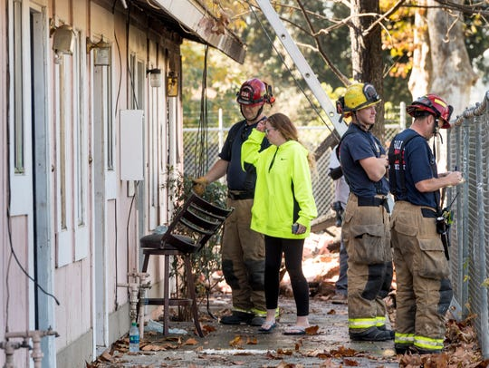 Kerrie Early, center, looks at damage from an apartment