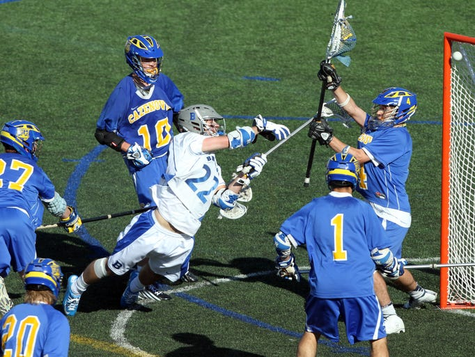 Bronxville's Harry Grass while surrounded by Cazenovia defenders, falls to the ground as he gets a shot off that gets by Cazenovia goalie Trevor Cross (4) and tied the game at 10 during the New York State boys lacrosse Class C championship game at Hofstra University in Hempstead, N.Y. June 7, 2014. Bronxville went on to win 13-10.