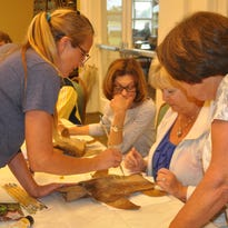 Artist Heidi Saletko shows Louise Mazzini, Lee Carpenter and Barbara Hill how to paint a turtle on a palm frond.