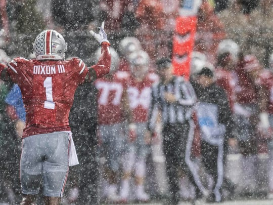 Ohio State receiver Johnnie Dixon celebrates in the rain after Ohio State's 52-14 victory over Illinois.