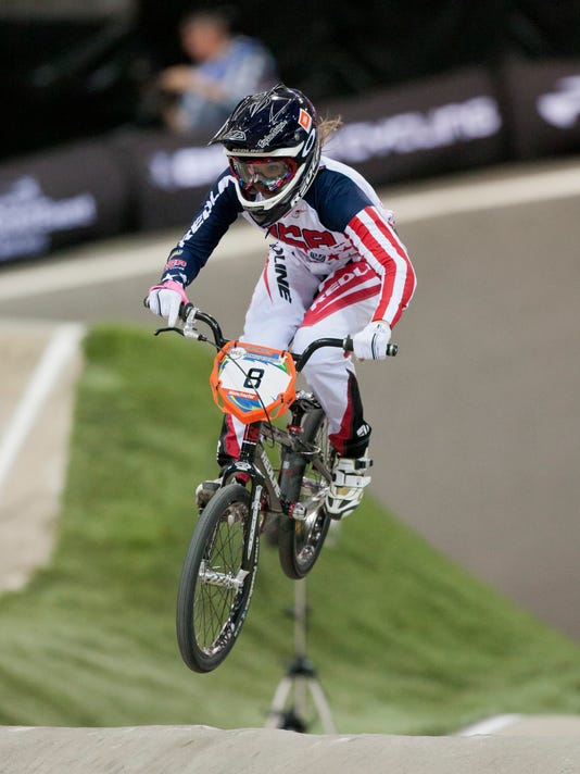 FILE - In this April 19, 2013, file photo, Alise Post, of the United States, rides to second place in the women's elite BMX Supercross World Championships in Manchester, England. Post is a top medal contender at the Olympics in Rio de Janiero . (AP Photo/Jon Super, FIle)