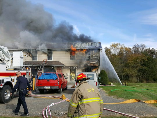 Firefighters at the scene of a working house fire in Cumberland Township on Oct. 28.