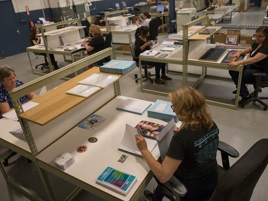 Workers check over and prepare finished portrait and panorama orders at BNL Enterprises in Marlboro on May 16, 2016