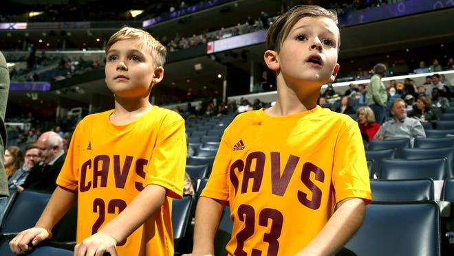 "Jax Mross and Braedyn Duffel, both 8, of Harrisburg, Ark.,  watch the Cleveland Cavaliers warm up for their game against the Grizzlies. The game was Duffel's Christmas present and he was hoping to see LeBron James. When his father, Jeremy, broke the news to him that LeBron would not be playing Braedyn Duffel said, ""That's okay, maybe I can see Kevin Love."" Love also did not play for the Cavaliers."