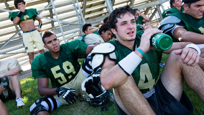 Chandler Basha wide receiver Hunter Dean-Gibson, right, and offensive lineman Jonathan Nathaniel, center, take a break with the team during football practice on July 30.