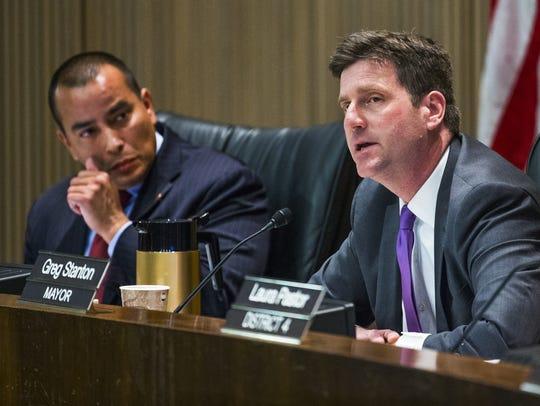 Phoenix City Councilman Daniel Valenzuela, left, listens