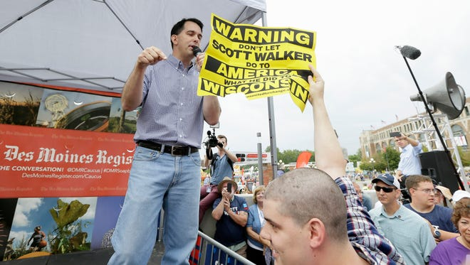 A protester holds a sign as Wisconsin Gov. Scott Walker speaks during a visit to the Iowa State Fair on Aug. 17, 2015, in Des Moines.