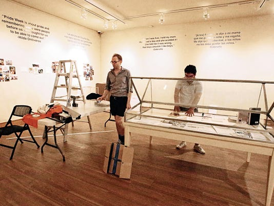 """Top photo: Volunteers install the """"Engendering Community"""" exhibit about the history of the area's LGBTQ community."""