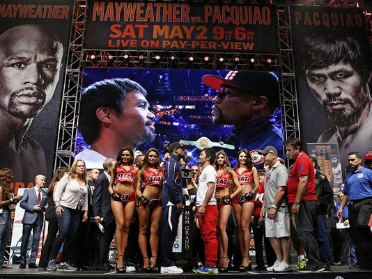 Floyd Mayweather Jr., center left, and Manny Pacquiao pose during their weigh-in on Friday, May 1, 2015 in Las Vegas. The world weltherweight title fight between Mayweather Jr. and Pacquiao is scheduled for May 2.